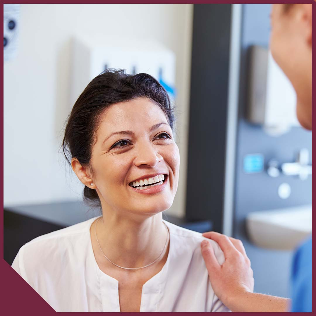 Smiling woman talking to doctor with doctor's hand placed on her shoulder.