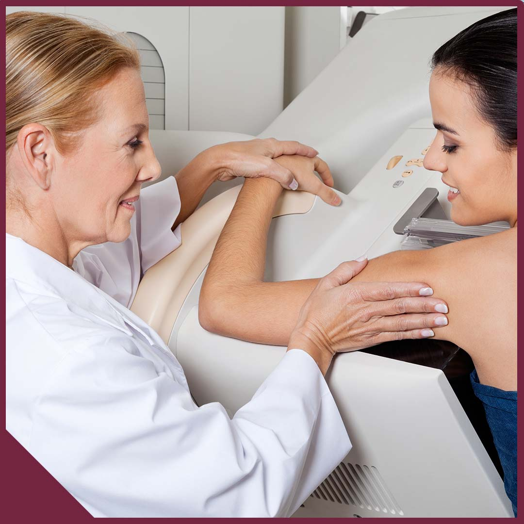 Mature female doctor assisting young patient during mammography.