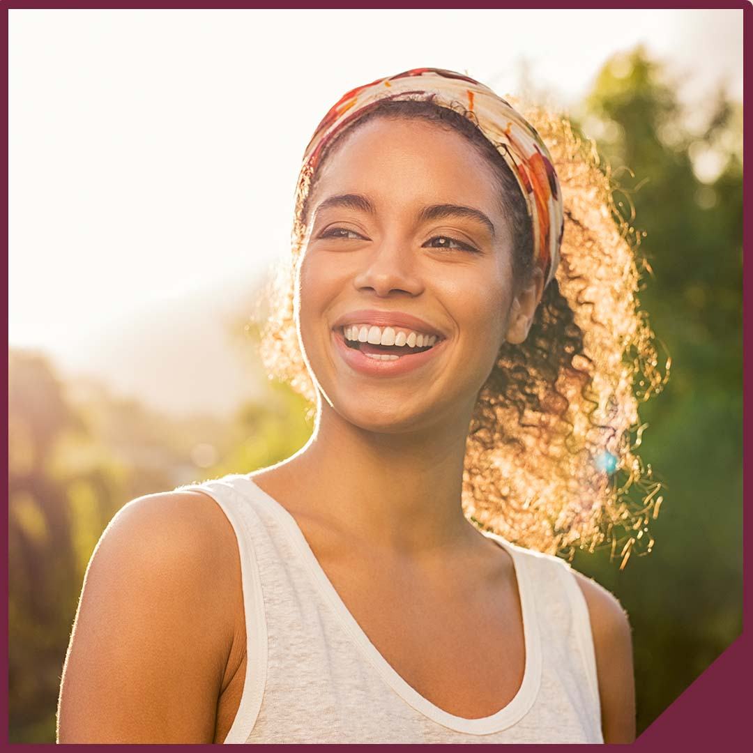 Portrait of a smiling young woman with the sun shining behind her.