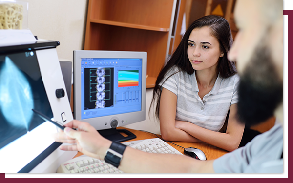 A radiologist showing a young patient an ultrasound view of her breast.